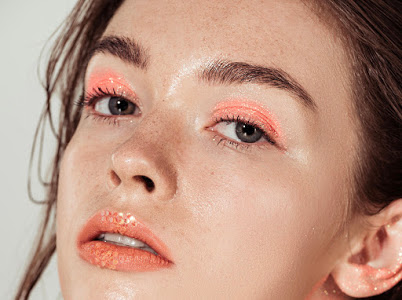 T1X4HT beautiful young woman with coral glitter makeup looking at camera isolated on grey